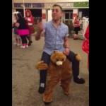 熊のぬいぐるみに肩車してもらう男
